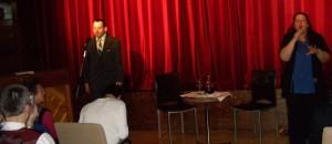 A Tárt Kapu Színház is készült egy  kis köszöntő műsorral. Lados Sándor látható a képen, aki verset mond. A közönség siket és nagyothalló tagjai számára jeltolmács segíti a megértést.